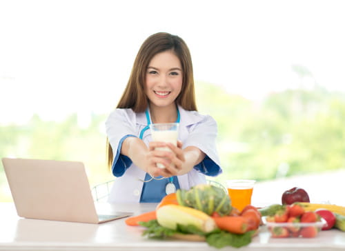 Marketing Digital para Nutricionistas: médica nutricionista oferecendo um copo de suco natural.